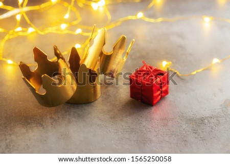 Three gold crowns and red gift box for concept of Epiphany or Dia de Reyes Magos ,  where in Spain giving gift a kids. #1565250058