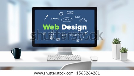 Web design text on computer display surrounded by sketch web page elements. Clean work desk with cup of coffee and plants.