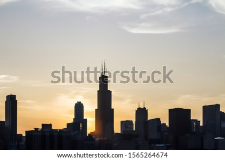 Backlit Chicago city skyline wallpaper at sunset. Urban architecture concept