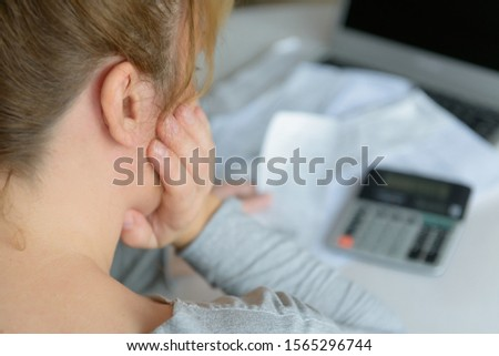 Woman uses a calculator to sum up expenses and holds her head worrying about the amount of money spent #1565296744