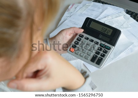 Woman uses a calculator to sum up expenses and holds her head worrying about the amount of money spent #1565296750