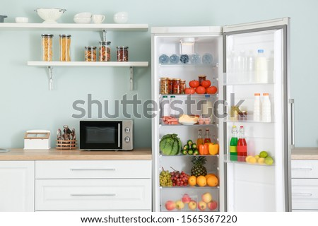 Open big fridge with products in kitchen #1565367220