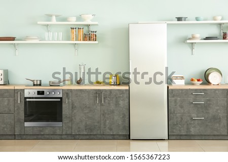 Big modern fridge in interior of kitchen Royalty-Free Stock Photo #1565367223