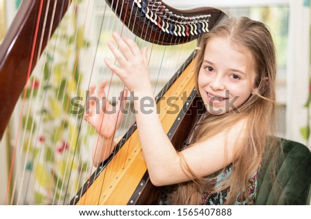 A young girl plays harp and looks at the camera with a smile Royalty-Free Stock Photo #1565407888