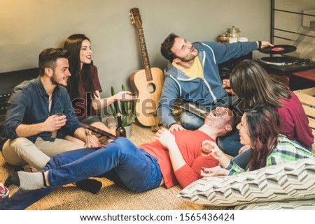 Happy friends having party listening vintage vinyl disc albums in hostel room - Young people having fun drinking shots and laughing together - Focus on left man face #1565436424