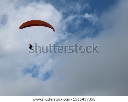 Paraglider in a day with clouds #1565439358