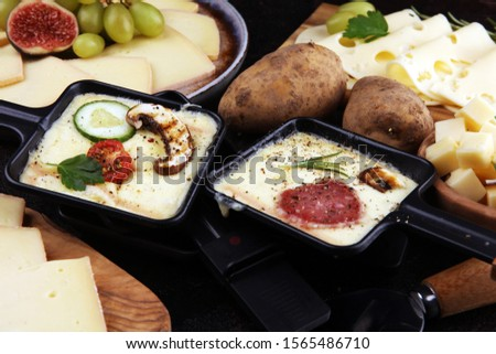 Delicious traditional Swiss melted raclette cheese on diced boiled or baked potato served in individual skillets with salami and potatoes #1565486710