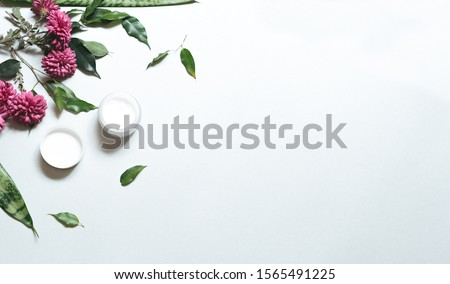 Natural cosmetics. Composition with body care products, wisp and green leaf and purple flowers over white background, top view,  FLAT LAY.    #1565491225