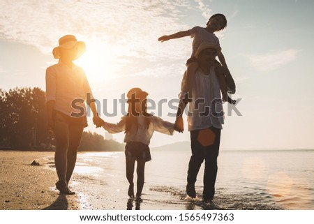 Holiday travel concept, Summer vacations. Happy family are having fun on a tropical beach in sunset. Father and mother and children playing together outdoor on sea. #1565497363