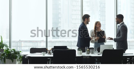 Businesspeople talking in office, standing against window by table, panorama, copy space Royalty-Free Stock Photo #1565530216