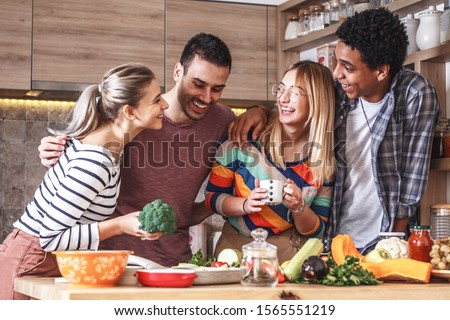 Group of friends preparing vegetarian meal.They preparing food and making fun in the  kitchen.