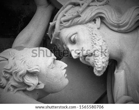 A moving monochromatic, black and white image of a statue of Jesus with Simon the Cyrenian, Stations of the Cross, Simon helping Jesus carry his cross.