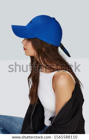 "Cropped side photo of a girl, wearing blue baseball cap with lettering ""none"", white tank top, black jacket and jeans with scuffs. On the strap in the back of cap is lettering ""untitled"".  #1565588110"
