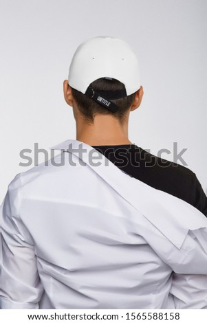 "Cropped back view shot of a dark-haired man, wearing white baseball cap with lettering ""untitle"" on the strap in the back of cap, black t-shirt and white shirt. He is posing on grey background.  #1565588158"