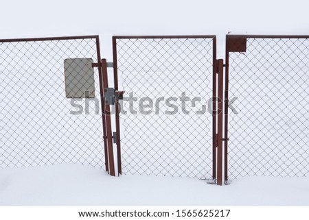 Fence and a wicket from a chain-link grid in snow. #1565625217