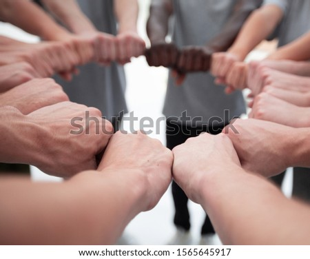 group of young people making a circle out of their hands #1565645917