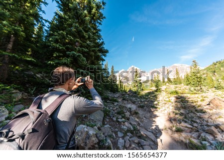 Maroon Bells peak in Aspen, Colorado with tourist man backpack hiker taking picture with camera in July 2019 summer on trail path road wide angle view