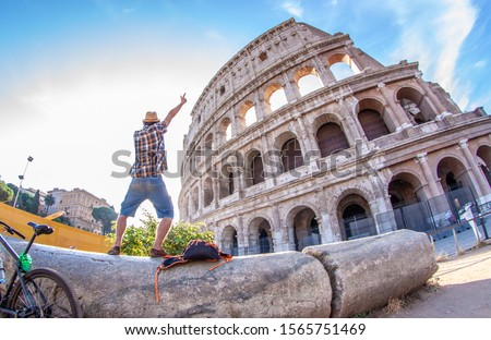 Happy young man tourist with bike wearing shirt and hat standing on a column taking pictures at colosseum in Rome, Italy at sunrise.