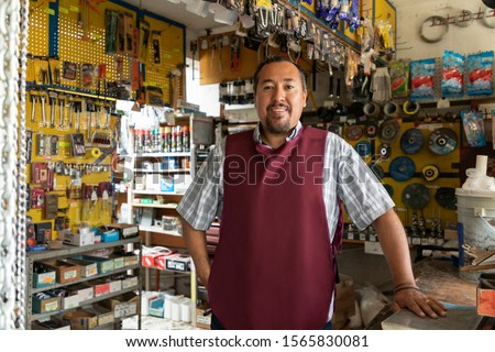 Smiling real worker attending a hardware store. interior detail #1565830081