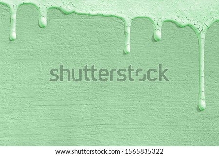 Monochrome background of the color of the trend 2020 neo mint with the texture of a concrete wall on which drops of paint froze. Fashionable concept, trend, color palette.