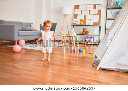 Beautiful caucasian infant playing with toys at colorful playroom. Happy and playful at kindergarten. #1565842537