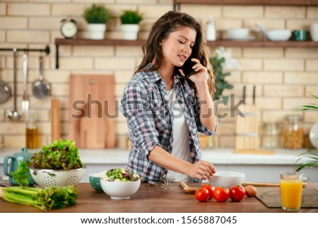 Beautiful girl talking on the mobile phone and smiling while cooking in kitchen at home #1565887045