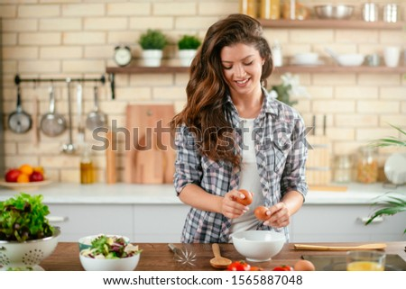 Beautiful young woman cooking in kitchen. Woman preparing pancakes. #1565887048