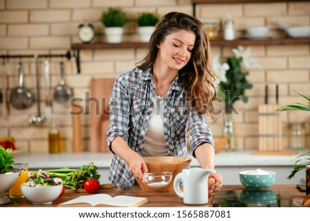Beautiful young woman cooking in kitchen. Woman preparing pancakes. #1565887081