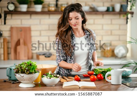 Portrait of beautiful young woman cooking in the kitchen.  Young Woman Cooking. Healthy Food - Vegetable Salad. #1565887087
