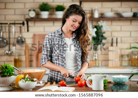 Portrait of beautiful young woman cooking in the kitchen.  Young Woman Cooking. Healthy Food - Vegetable Salad. #1565887096