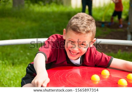 Boy on the tabletop shines and laughs into the camera #1565897314