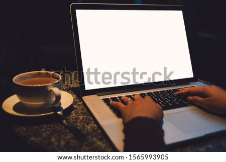 A cup of cappuccino coffee with laptop white screen on table. Royalty high quality free stock photo image of coffee cup with laptop for working in a coffee shop, typing with blank screen white color