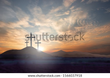 Three crosses on the mountain Jesus Christ with a sunset background Royalty-Free Stock Photo #1566037918