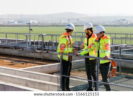 Engineers assesing wastewater plant performance from platform #1566125155