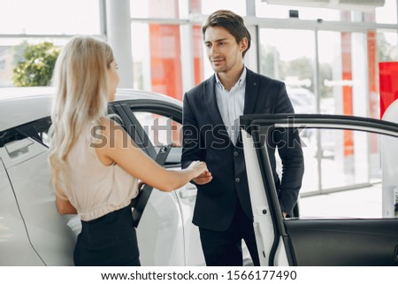 Couple in a car salon. Family buying the car. Elegant assistant with handsome man #1566177490