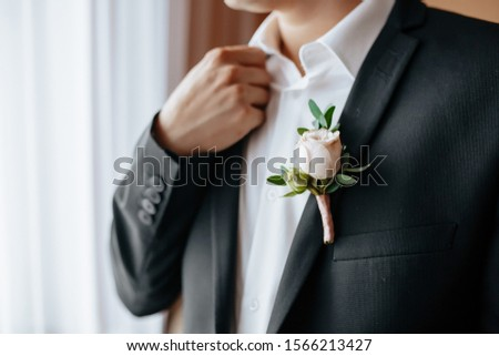 the groom in a black jacket and in an unbuttoned white shirt without a tie and without a butterfly with a boutonniere of delicate pink flowers is standing in the room of the house  #1566213427