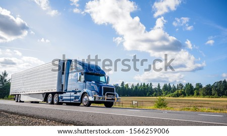 Big rig powerful professional industrial blue bonnet semi truck for long haul delivery commercial cargo going with refrigerator semi trailer on the summer road with forest and meadows on the sides #1566259006