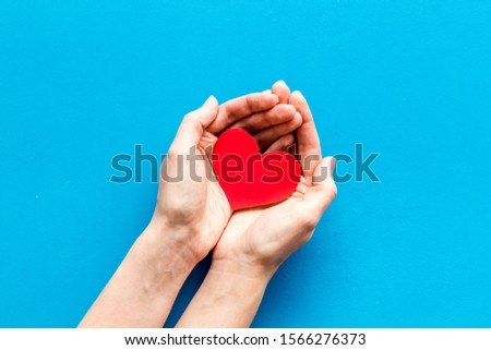 Heart icon. Paper heart in hands on blue background top view copy space #1566276373