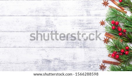 Christmas background with fir tree, spice and red holly on wooden table. Snowfall drawing effect. Horizontal banner. Horizontal banner. Top view Copy space - Image #1566288598