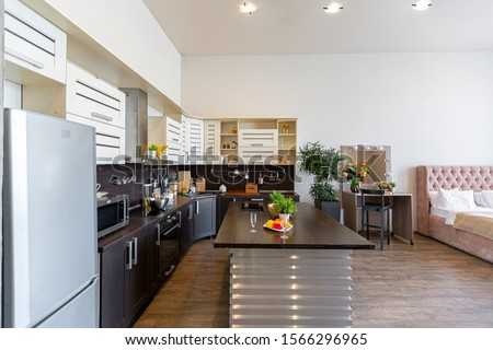 Contemporary ordinary design of spacious studio in soft warm colors. Simple furniture. Light large room with sunlight. Daytime. Tiled brown floor and white walls . #1566296965