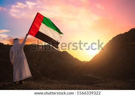 Emirati Arab man holding UAE flag, celebrating the national day #1566339322