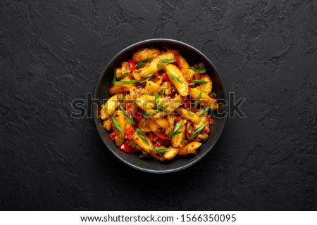 Baby Corn Manchurian dry looks like Schezwan Baby Corn in black bowl at dark slate background. Baby Corn Manchurian - is indo chinese cuisine dish with deep fried corn, bell peppers, sauce and onion. #1566350095