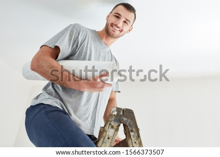 Young man with wallpaper on a ladder while wallpapering and renovating in new home #1566373507