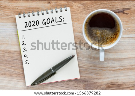 White notebook for notes, pen, wooden background. Top view Copy space, 2020 Goals text concept. #1566379282