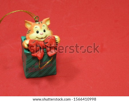"""A cute little toy cat coming out of a Christmas gift box with a big red bow. On the box is written """"Merry Christmas"""". Time for happiness and giving. Red background. #1566410998"""