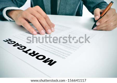man wearing a suit sitting in a table signing mortgage loan contract #156641117