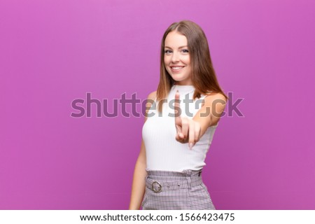young red head woman smiling proudly and confidently making number one pose triumphantly, feeling like a leader against flat wall #1566423475