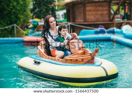 Son and mother spending time in the amusement park. #1566437500