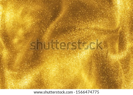 Abstract elegant, detailed gold glitter particles flow with shallow depth of field underwater. Holiday magic shimmering luxury background. Festive sparkles and lights. de-focused. #1566474775