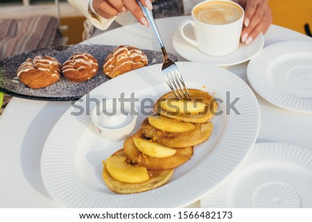Tasty picture of delicious pancakes with apple pieces on it. Plate with eclair besides. Good tasty morning. Woman hold for and touch white cup with coffee. Cut view